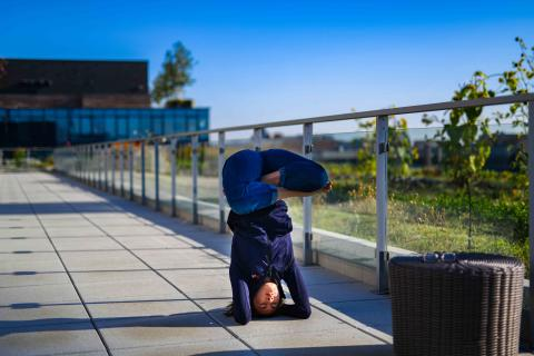 inverted upside down yoga lotus position in rooftop garden